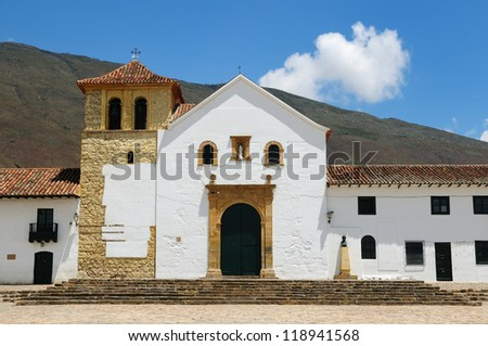 Colombia, Beautiful white villa with shingle roofs hidden behind walls in colonial Villa de Leyva. Parish church on the plaza central