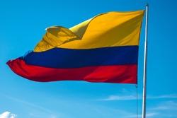 Colombia flag on a pole against blue sky
