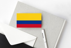 Colombia flag on minimalist letter background. National invitation envelope with white pen and notebook. Communication concept.