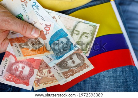 Colombian money, pesos, held in the hand together with the national flag. Economics concept  Foto stock ©