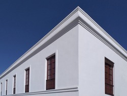 Colonial building corner with white walls, wooden windows under a deep blue sky. Corner architecture of white building with blue sky background. Perspective and underside angle of building facade.