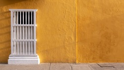 Colonial facade with ocher or yellow wall and window with white balusters, ideal for background, Cartagena de Indias, Colombia