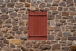 Colonial Pennsylvania construction stone wall exterior facade with closed architectural feature antique red wooden window shutters. Excellent texture and historic feel with copy space