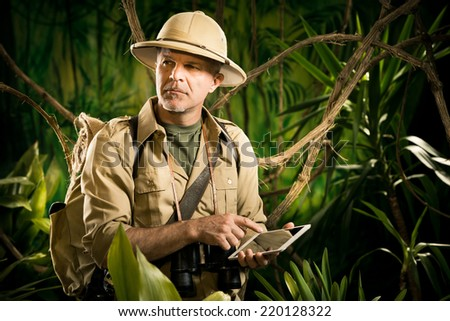 Colonial style adventurer with digital tablet exploring jungle wilderness