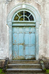 colonial style door in light blue color, well worn and old with ladder in front