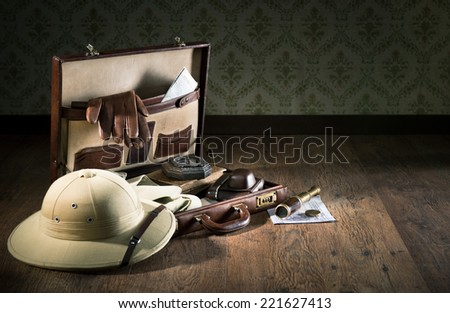 Colonial style explorer packing with open leather briefcase, pith hat, leather gloves, maps and brass telescope.