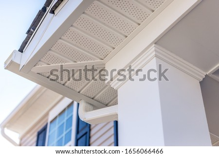 Colonial white custom porch columns with wood looking vinyl column wrap, sheets and molding, white soffit provides optimal ventilation for roof overhangs   Stock photo ©