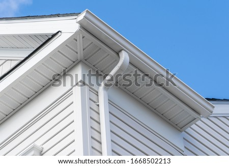 Colonial white fiber cement horizontal vinyl lap siding, soffit with ventilation,  gutter and guard, eaves with elbow, drip, on a new construction American single family home Stock photo ©