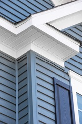 Colonial white   soffit providing ventilation to the attic, with pacific blue vinyl horizontal siding, blue shutter at a luxury American single family home neighborhood USA