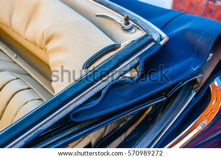 Color and beauty of vintage cars. Convertible top of an old luxury automobile. Leather seats. Vibrant colors. #570989272