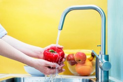 Color and bright shot as a young woman thoroughly washes vegetables in the kitchen. Vegetable preparing to eat you need to wash