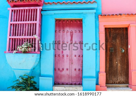 Color blocking pink and blue colonial house facades in the walled, historic old town of Cartagena de Indias in Colombia