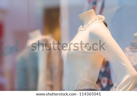 Color blouses on mannequins under shopping window in mall