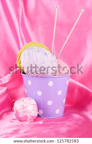 Color bucket with multicolor  balls of tread on color fabric background