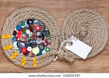 Color buttons in rope frame on wood