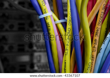 Color cables in the back of the server rack with black and white background out of focus