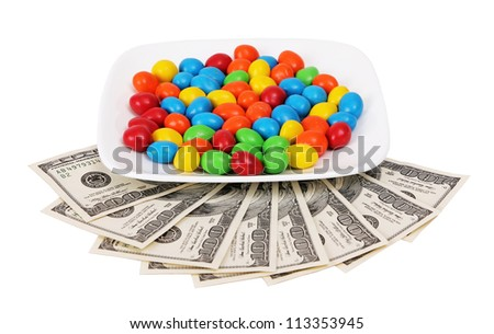 color candy on plate with money isolated on white background