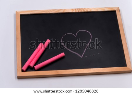 Color chalk put and draw cartoon heart shape on blackbroad.Tell love in valentine day or tell save good health and heart. #1285048828