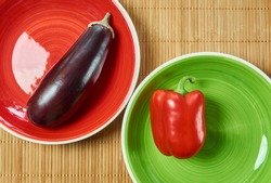 color contrasting still life - purple eggplant on a red plate and red bell pepper on a green plate next on a cane serving mat