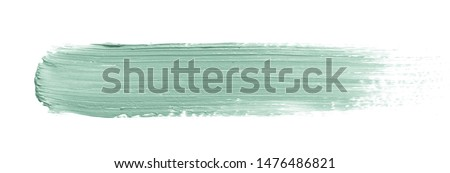 Color corrector stroke isolated on white background. Green color correcting concealer cream smudge smear swatch sample. Makeup base creamy texture
