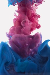 Color drop in water, photographed in motion. Ink swirling in water. Cloud of silky ink in water isolated on white background. Colorful ink in water, ink drop. Pink, blue