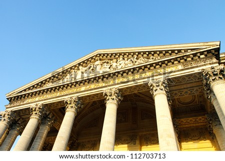 Color DSLR image looking up at the facade of the Pantheon in Paris, France, with a blue sky background and copy space for text. Ancient, landmark building is popular tourist destination.