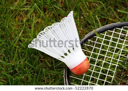 Color DSLR image of a white and red badminton shuttlecock or birdie and racket on green grass. Popular summer backyard sport. Horizontal with copy space for text.