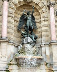 Color DSLR image of ancient landmark Fontaine Saint-Michel, Paris, France, with flowing water. St. Michel Fountain is a popular Left Bank tourist attraction. Vertical.