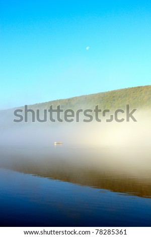 Color DSLR image of Canadice Lake, a New York Finger Lake, at dawn, with mist and a boater through the fog over still, calm water. Vertical with copy space for text.