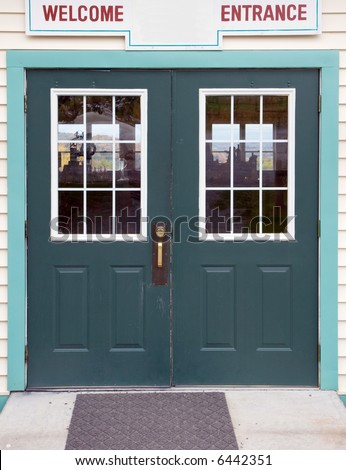 Color DSLR image of green store entrance doors, with the sign welcome over them.