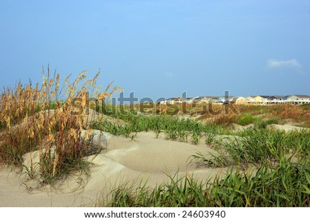 Color DSLR image of luxury vacation beach houses seen across the green grass covered sand dunes, Sunset Beach, North Carolina. Horizontal orientation with copy space for text.