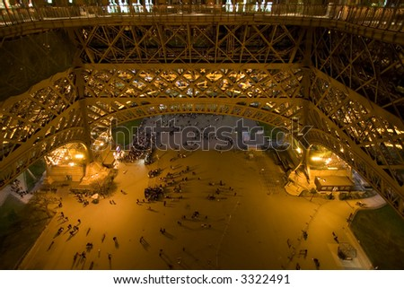 Color DSLR image of the plaza beneath the Eiffel Tower at night, Paris France. Tower is a landmark, monument and popular tourist destination, as see by people in the pools of light. Horizontal.
