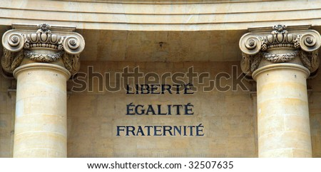 Color DSLR image of words in French, saying Liberty, Equality, and Fraternity on a granite wall, flanked by columns; the motto of the French Revolution. Horizontal with copy space for text.