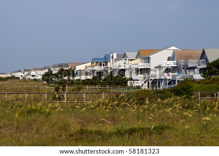 Color DSLR landscape image of luxury vacation beach houses at the edge of the green grass covered sand dunes, Sunset Beach, North Carolina. Horizontal with copy space for text.