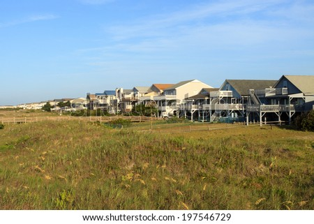 Color DSLR landscape picture of luxury beach vacation houses along the green, grass covered sand dunes; Sunset Beach, North Carolina.  The homes horizontal with blue sky and copy space for text.