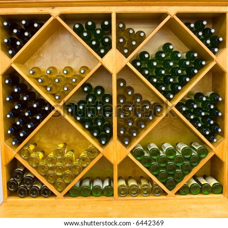 Color DSLR picture of geometric wine rack with multiple bottles of red and white wine lying in storage in a store for sale.  Horizontal orientation.