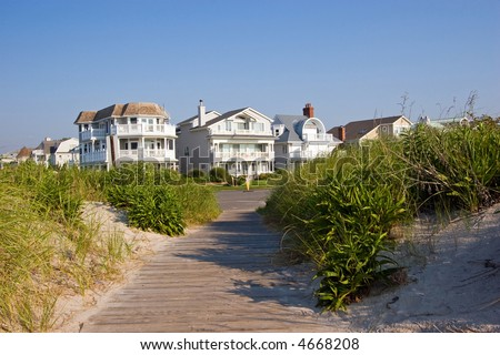 Color DSLR picture of luxury vacation beach houses along the New Jersey shore, with grass covered sand dunes in the foreground and clear blue sky background. Horizontal with copy space for text.