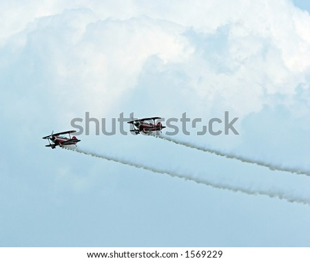 Color DSLR picture of two stunt planes at an airshow.  Biplanes are speeding horizontally, trailing white smoke contrails against cloudy sky. Airplanes are dangerous and fast.  Copy space for text.