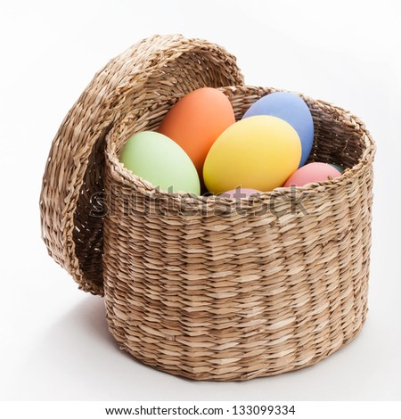 color eggs in wicker basket for holiday easter on white background