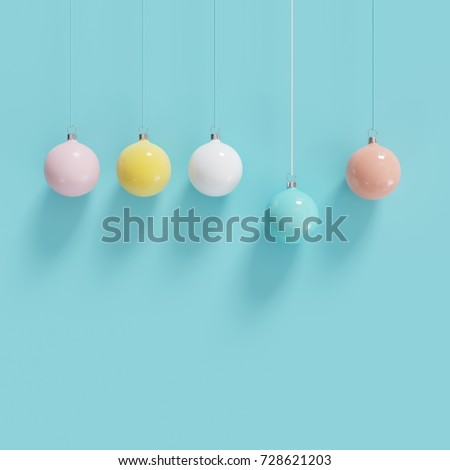 Color full christmas ball Ornaments hanging on blue background. minimal christmas concept.