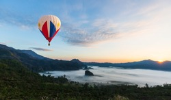 color hot air balloon over the clouds and mountain in the morning time