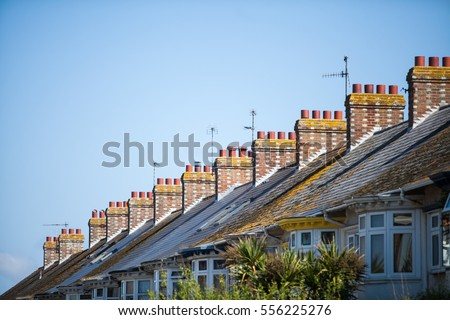Color image of a typical English row of houses with chimneys.