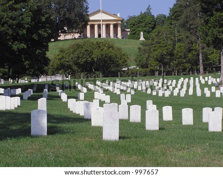 Color image of Arlington National Cemetery, with white memorial headstones marking graves in the green lawn and the Robert E. Lee house in background.  Horizontal orientation with copy space for text