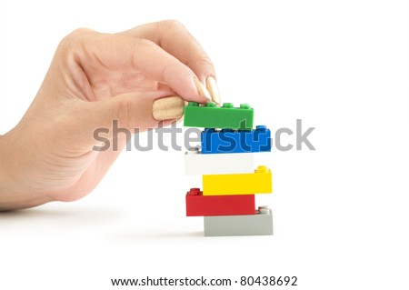 color lego bricks with hand isolated on white