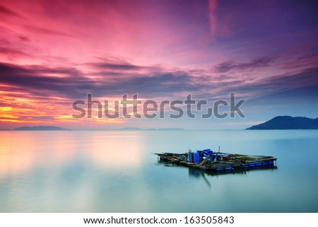 color of sunrise at fish cage...