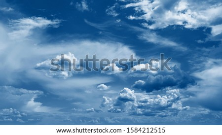 Color of the year 2020 classic blue. Classic blue sky with clouds in summer sunny day. Beautiful natural background with space for text. Fashionable pantone color trend concept