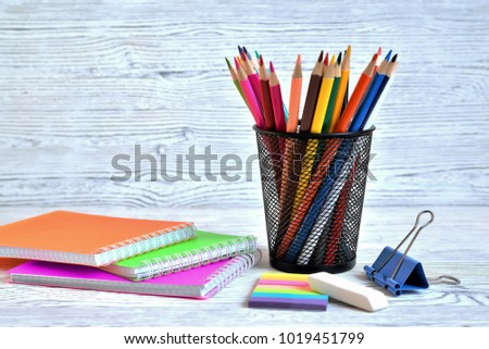 Color pads and colored pencils in a container, eraser and paper clip on an aged white background