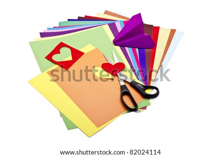 Color paper sheets with scissors and paper craft isolated on white