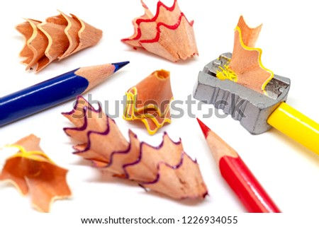 Color pencil and prism sharpener macro photo on white background. Drawing as hobby banner template. Sharpening pencils concept. Yellow, red and blue crayons closeup. Children creative development