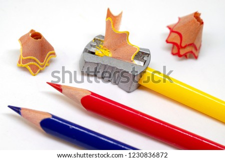 Color pencil and prism sharpener macro photo on white background. Drawing as hobby banner template. Sharpening pencils concept. Yellow, red and blue crayons closeup. Children art class creative hobby
